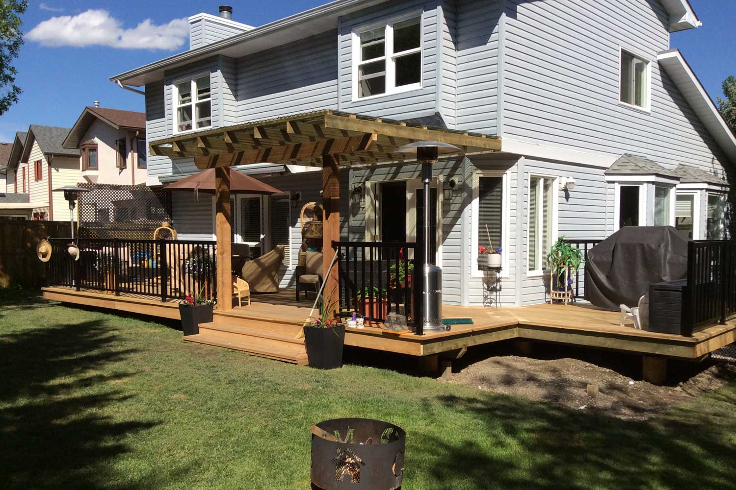 a photo of a backyard with a fire pit, wooden deck and pergola